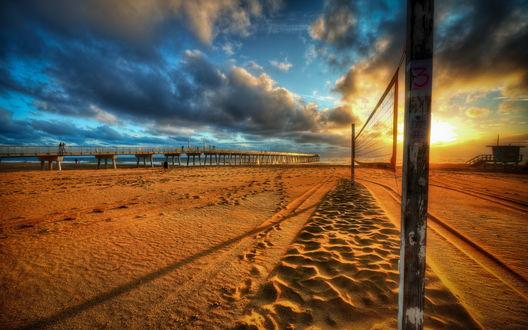 Обои Песчаный пляж с натянутой между двумя деревянными столбами сеткой для пляжного волейбола, на берегу морского залива на рассвете, каменным мостом, уходящим в море