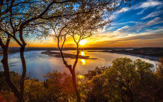 Обои Золотистые, солнечные лучи на утреннем, синем небосклоне с белыми облаками, осветили водную гладь озера с песчаной косой, деревьями, растущими на берегу