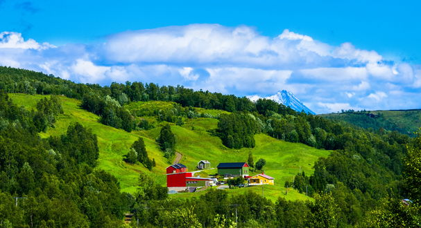 Обои Несколько домиков, стоящих на зеленых холмах в окружении деревьев, с подходящей к ним грунтовой дорогой на фоне заснеженных пиков гор и синего неба с белыми, кучевыми облаками