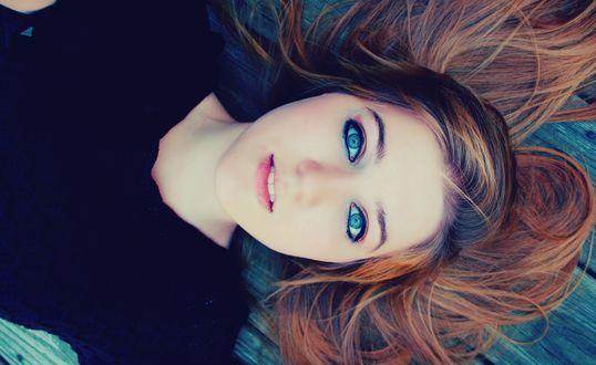 Обои Красивая девушка лежит на спине с распущенными волосами и смотрит голубыми глазами