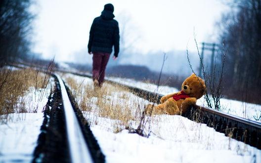 Обои Человек, идущий по заснеженному, железнодорожному полотну с лежащим позади него у рельсы плюшевым медведем на фоне серого небосклона, затянутого туманной дымкой