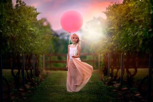 Обои Милая, белокурая девочка, держащая в руке надувной, воздушный шарик, идущая по аллее парка на рассвете в ослепительных, солнечных лучах