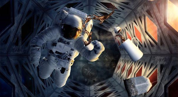 Обои Космонавт в скафандре летает в невесомости внутри космического корабля, держит в руке чашку пытаясь попить чая. Рядом летает кувшин с чаем и пакетик с заваркой чая