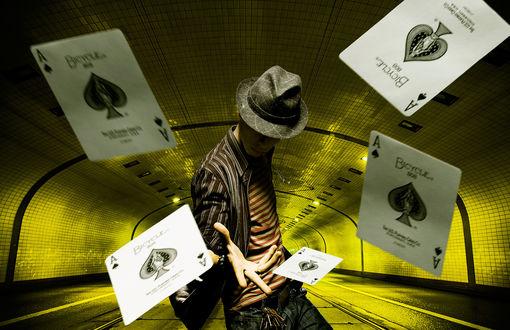 Обои Мужчина в шляпе стоя в туннеле выбросил рукой игральные карты, четыре туза