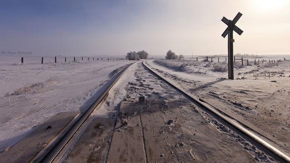 Обои Железнодорожное полотно, проходящее по заснеженному полю с предупреждающим знаком, стоящим у обочины на фоне пасмурного небосклона