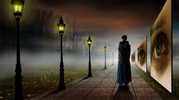 Обои Девушка в длинном пальто, идущая по тротуару, с одной стороны которого расположен ряд зажженных фонарей, с другой стороны ряд афиш с нарисованными человеческими глазами, фотограф Бен Гуссенс / Ben Goossens