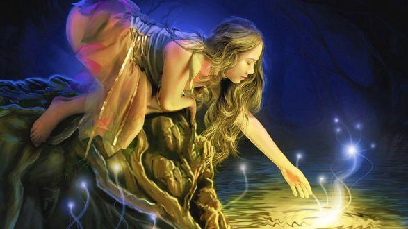 Обои Девушка стоя на коленях на камне, протянула руку к светящемуся предмету на воде