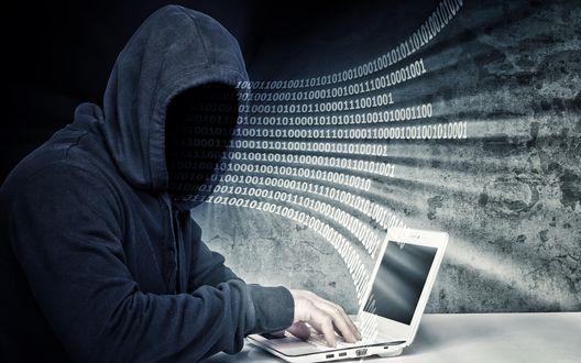 Обои Хакер в курточке с капюшоном и затемненным лицом сидит за ноутбуком, извлекая из него миллионы байт информации