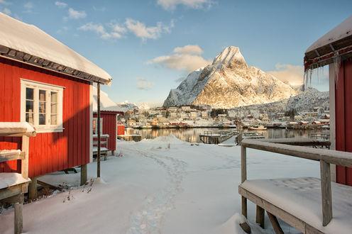 Обои Рыбацкий поселок, стоящий на скалистом, заснеженном берегу морского залива на фоне синего неба с белыми, кучевыми облаками, Норвегия / Norway