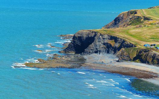 Обои Скалистый берег моря с палаткой, автомобилями и людьми на его травяной поверхности