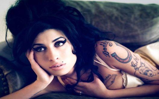 Обои Английская певица Эми Уайнхаус / Amy Winehouse / с тату на руке лежит на диване