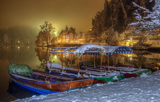 Обои Лодки, стоящие у заснеженной набережной незамерзающего зимой водоема городского парка на фоне ночного небосклона