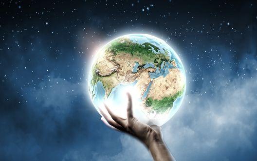 Обои Рука держит планету Земля на фоне ночного неба