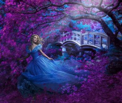 Обои Актриса Лили Джеймс / Lily James в легком, воздушном, синем платье, стоящая под деревом с сиреневыми листьями на берегу водоема с проложенным через него пешеходным мостиком, автор Nataliorion