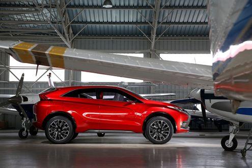 Обои Автомобиль модели Mitsubishi Concept XR-PHEV II стоит в ангаре для частных самолетов