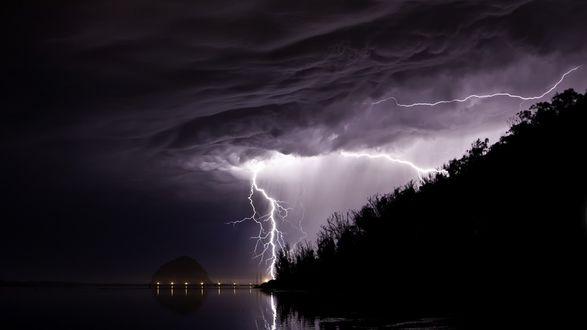Обои Природа, грозовые тучи покрыли все небо, циклон, молния, лес от непогоды стоит черным, ночь, море замерло, вдали виднеются огоньки города на фоне горы