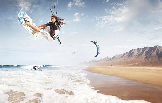 Обои Девушка кайтсерфингистка взлетела высоко над волнами
