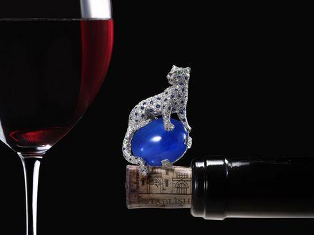 Обои Украшение в виде леопарда сидящего на синем шаре, находится на пробке бутылки вина, рядом стоит фужер с красным вином, компьютерная графика