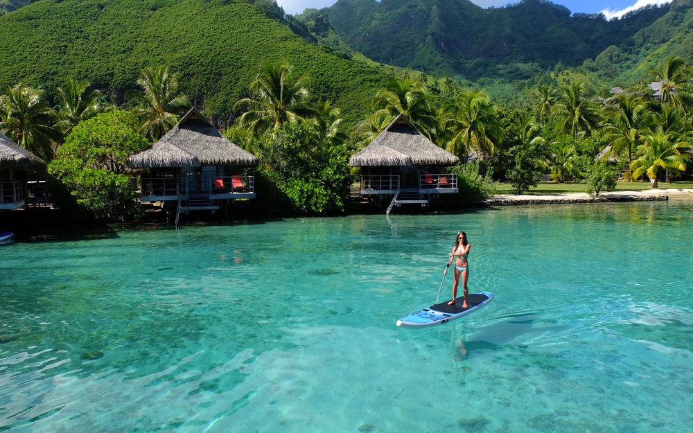 Обои для рабочего стола Девушка, держащая в руке деревянный шест, стоящая на доске для серфинга, плывущая по лазурной, прибрежной воде со стоящими на берегу бунгало, утопающими в зелени пальм на фоне гор