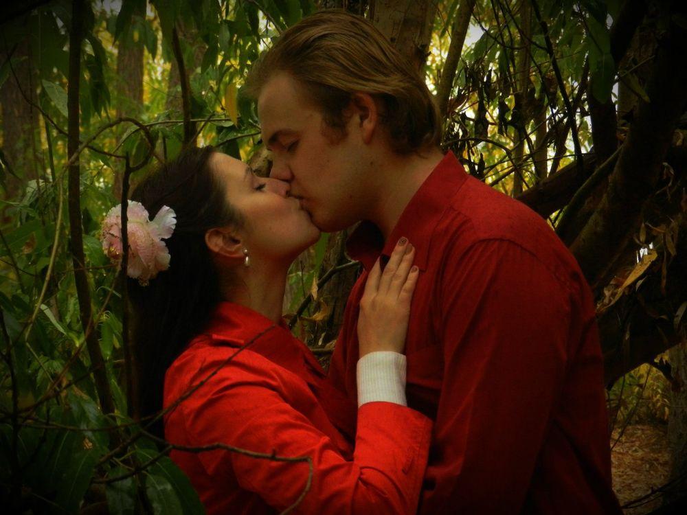 Обои для рабочего стола Двое влюбленных в красной одежде целуются в чаще леса