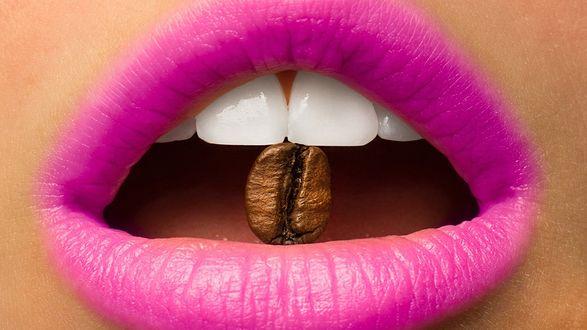 Обои Открытый девичий рот с алыми губами и зернышком кофе в зубах