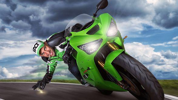 Обои Крутой гонщик на зеленом мотоцикле, на повороте нагнувшись поджигает об асфальт спичку, для подкуривания сигареты у себя во рту