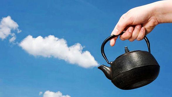 Обои Рука с черным чайником, с носика которого идет пар