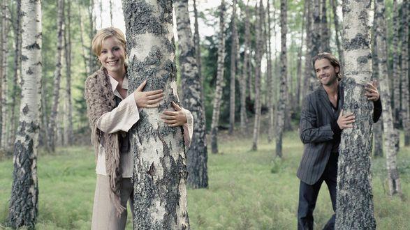 Обои Влюбленные парень и девушка обнимают стволы березок