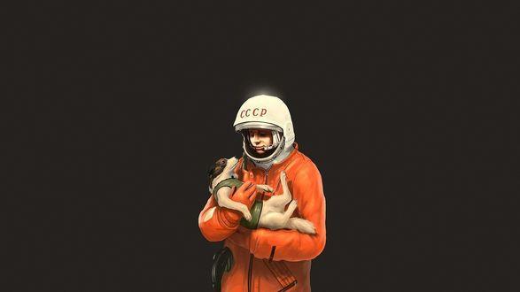 Обои Первый космонавт Юрий Гагарин в скафандре, держит на руках одну из первых собачек, слетавшую в космос