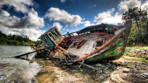 Обои Старый полу разрушенный баркас лежит на берегу