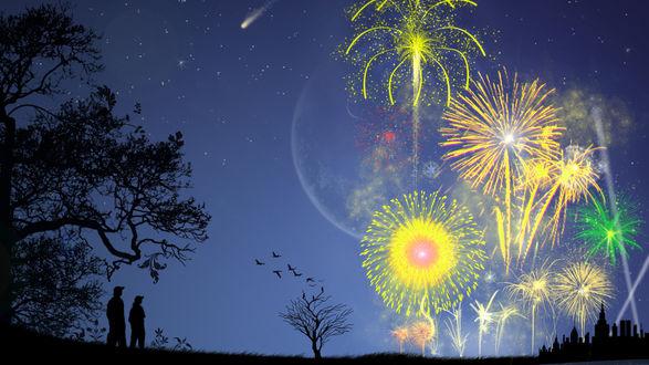 Обои Люди стоят в темноте под деревьями и смотрят, как на небе загораются вспышки праздничного салюта