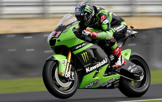 Обои Мотогонщик на зелено-черном байке Kawasaki мчит по трассе