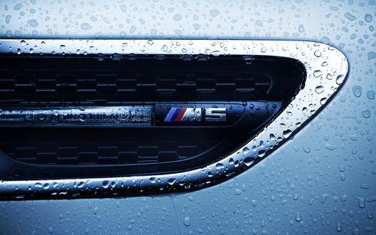 Обои Шильдик фирмы BMW M5 на крыле авто, в каплях воды