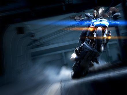 Обои Мотоциклист в экипировке поднял мотоцикл на заднее колесо и мчится в тоннеле с размытым фоном