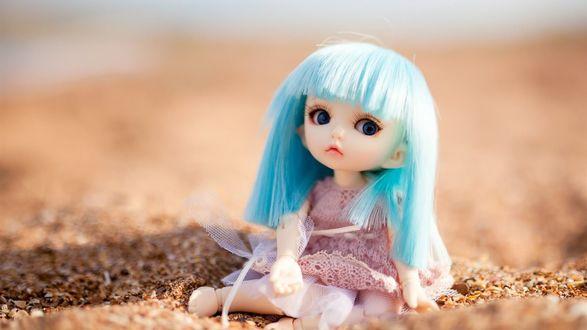 Обои Кукла с голубыми волосами сидит на песке