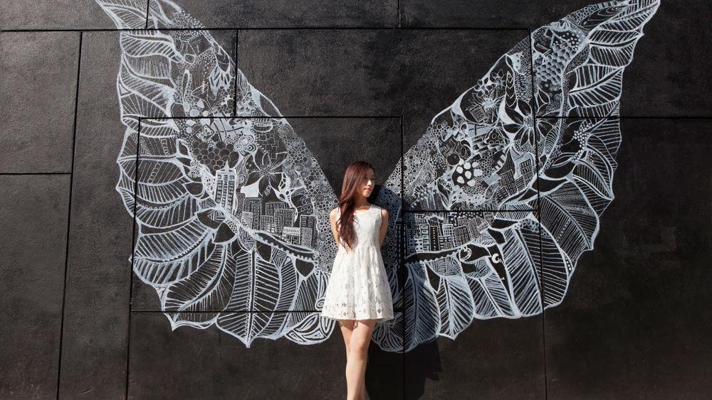 Обои для рабочего стола Девушка, с нарисованными на стене крыльями