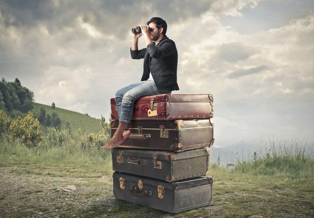 Обои для рабочего стола Мужчина, сидя на стопке из чемоданов, смотрит вдаль через бинокль