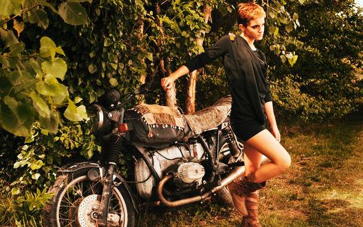 Обои Актриса Emma Watson в черном платье позирует рядом с мотоциклом на фоне кустов и деревьев