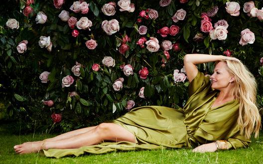 Обои Певица Emma Bunton лежит на траве в зеленом платье рядом с кустами цветущих роз