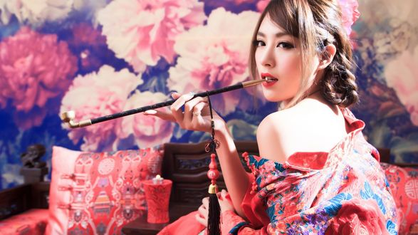 Обои Азиатка курит среди цветов