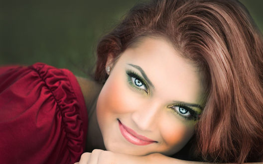 Обои Девушка с длинными каштановыми волосами в бордовой блузке опустила голову на кисть руки и улыбается