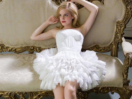 Обои Актриса Emma Watson в белом платье лежит на диване