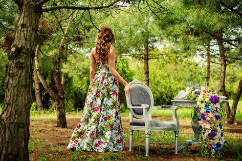 Обои Девушка с длинными вьющимися русыми волосами в летнем белом платье с яркими цветами стоит спиной к нам, положив руку на белое кресло, которое стоит рядом со столиком с цветами в лесу. Фотограф Анна Асланян