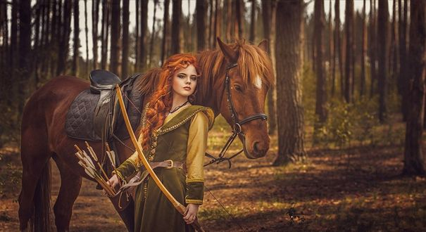 Обои Рыжеволосая девушка с луком и стрелами стоит рядом с рыжим конем в лесу