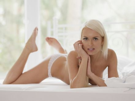 Обои Полуобнаженная девушка позирует лежа на кровати