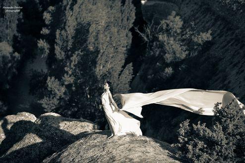 Обои Девушка в белом платье стоит на скале и держит в руках за спиной развевающуюся белую ткань. На скале слева отображается тень девушки в виде ангела. Модель Алиме. Фотограф Александр Друкар