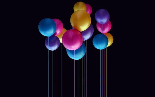 Обои Разноцветные воздушные шарики на нитках парят на черном фоне