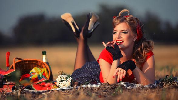 Обои Гламурная девушка лежит на скошенной поляне в ожидании любимого на пикник на размытом фоне деревьев