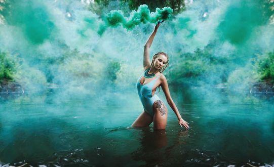 Обои Девушка в голубом купальнике с татуировкой на ноге стоит в воде на фоне дыма