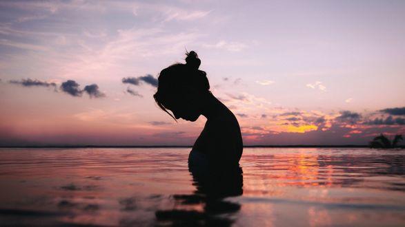 Обои Девушка склонила голову в морской глади на закате солнца